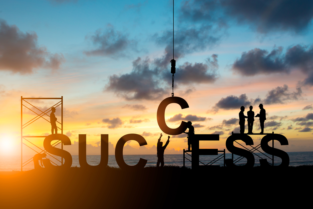 team of people constructing the word success against a sunset background
