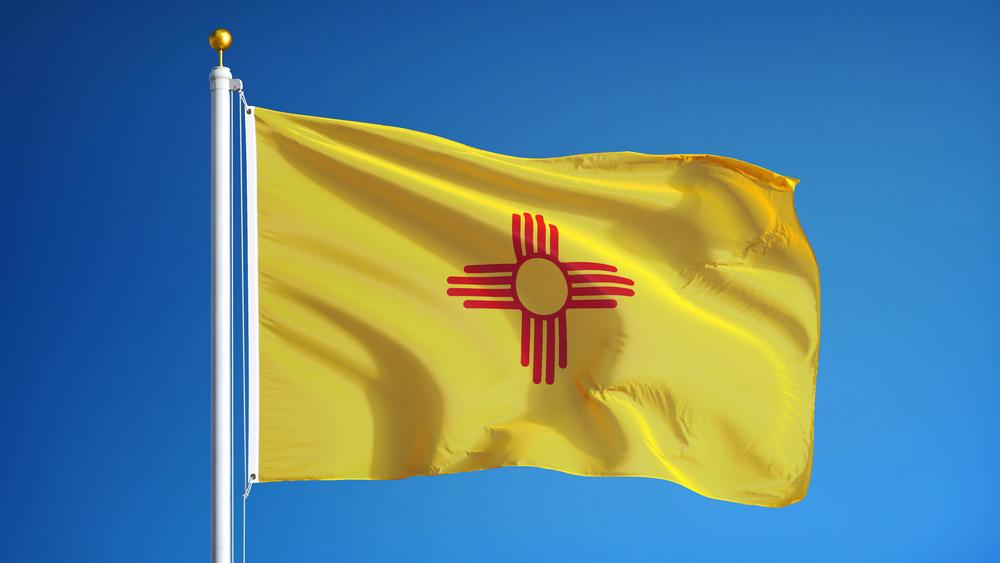 New Mexico flag on pole against blue sky backdrop