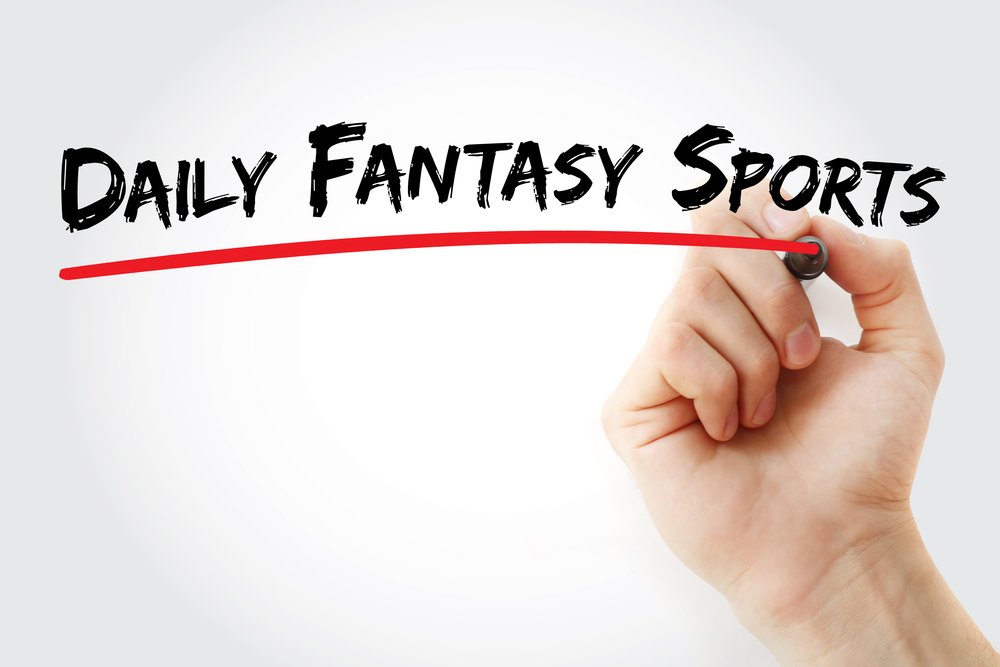 hand underscores the words daily fantasy sports in red pen