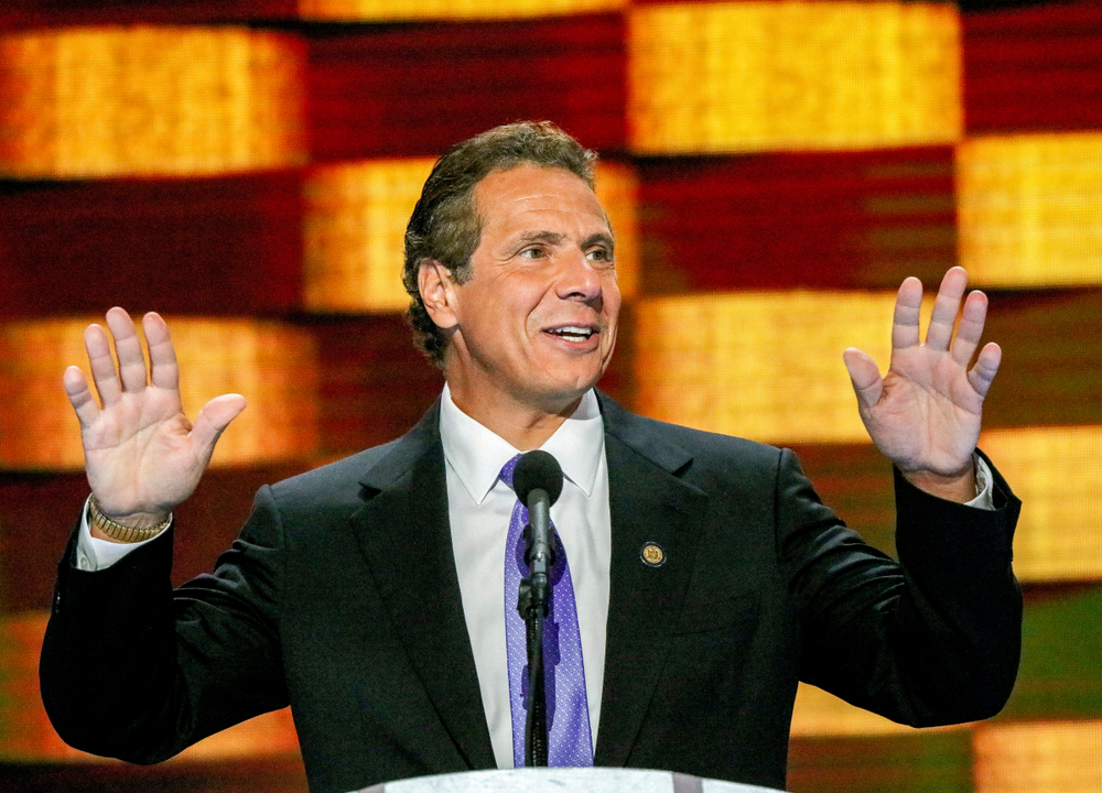 New York Governor Andrew Cuomo holds hands up while addressing a conference