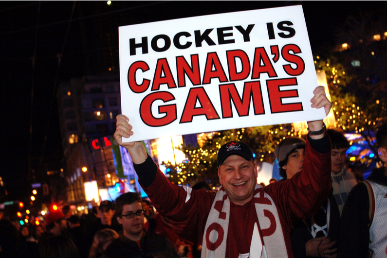 """Man holding up a sign reading """"Hockey is Canada's Game"""""""