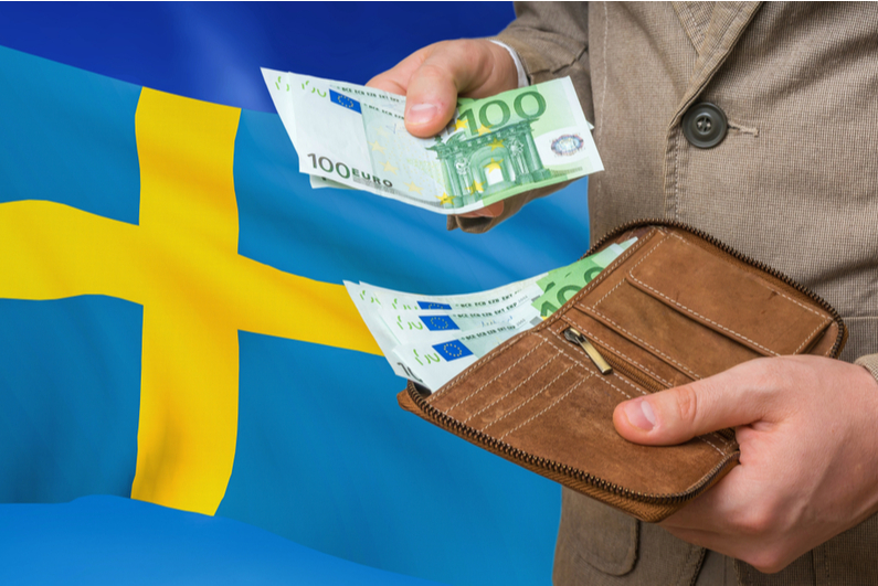 Man taking money out of his wallet in front of the Swedish flag