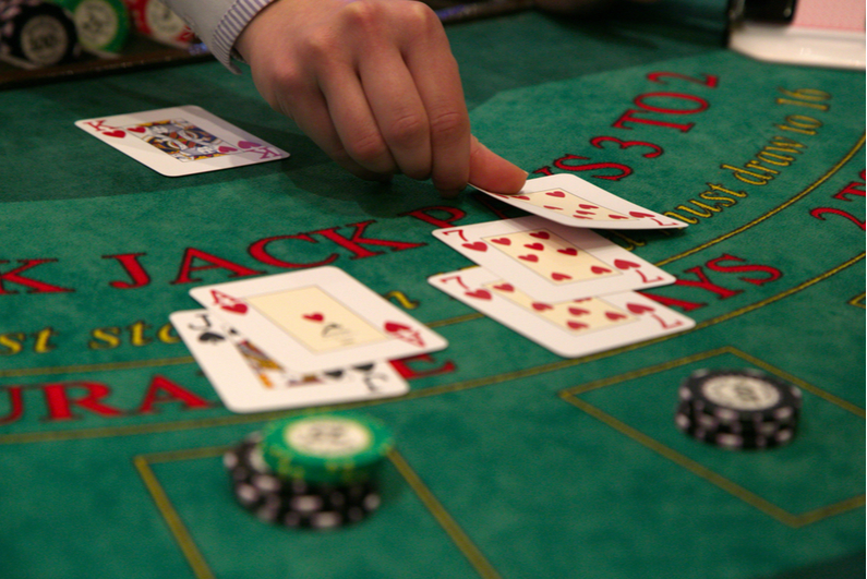Blackjack dealer laying a third red 7 for a player
