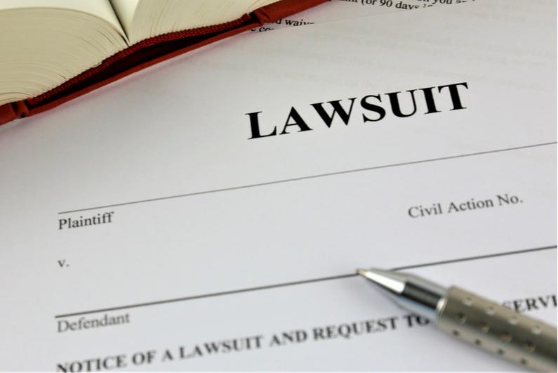 Pen resting on a black lawsuit document