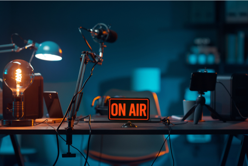 """Podcast desk setup with """"ON AIR"""" sign"""