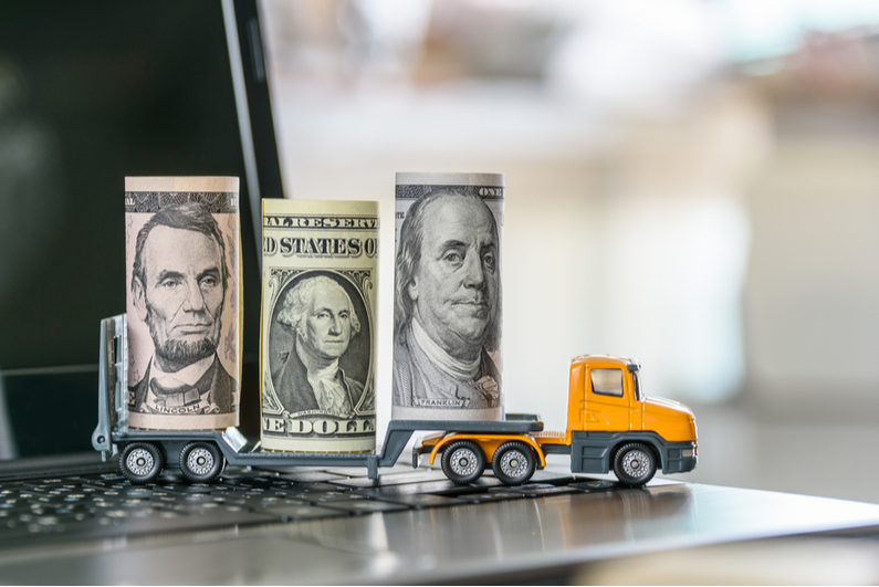Toy truck on a laptop carrying roles of cash