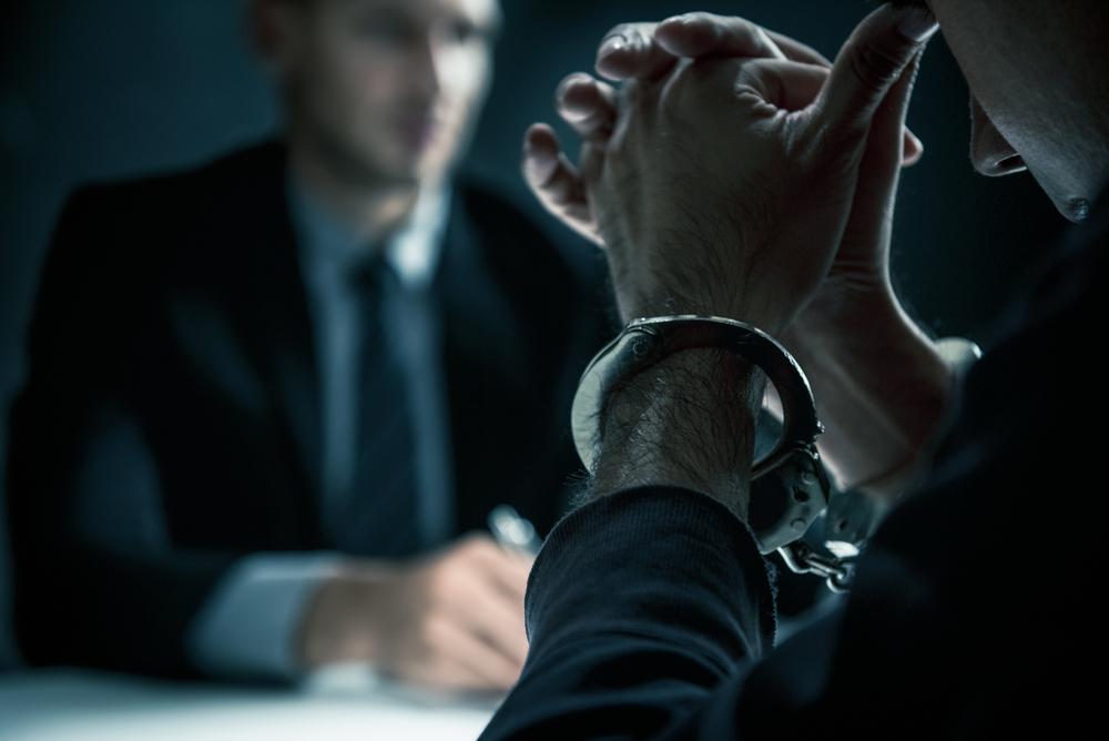 Man in handcuffs sits opposite an attorney