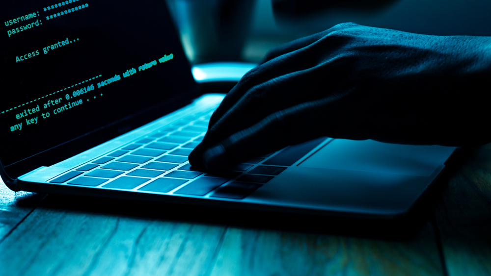 A person hacking into a user account on a laptop