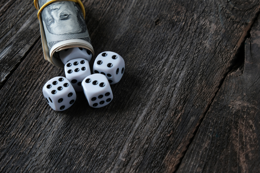 Gaming dice in a roll of US cash