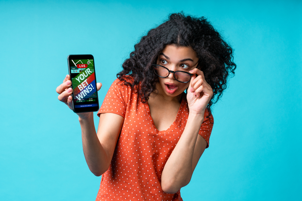 Curly-haired female with glasses uses a betting app on her mobile phone