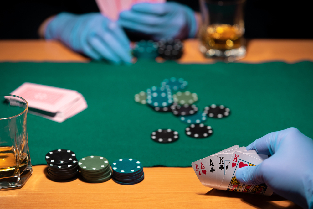 Two people play poker wearing surgical gloves