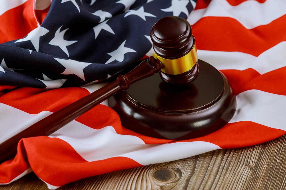 A judge's gavel resting on the US flag