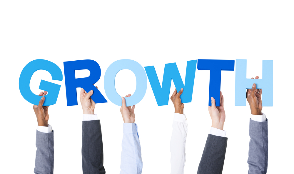businesspeople's hands hold up letters that spell growth