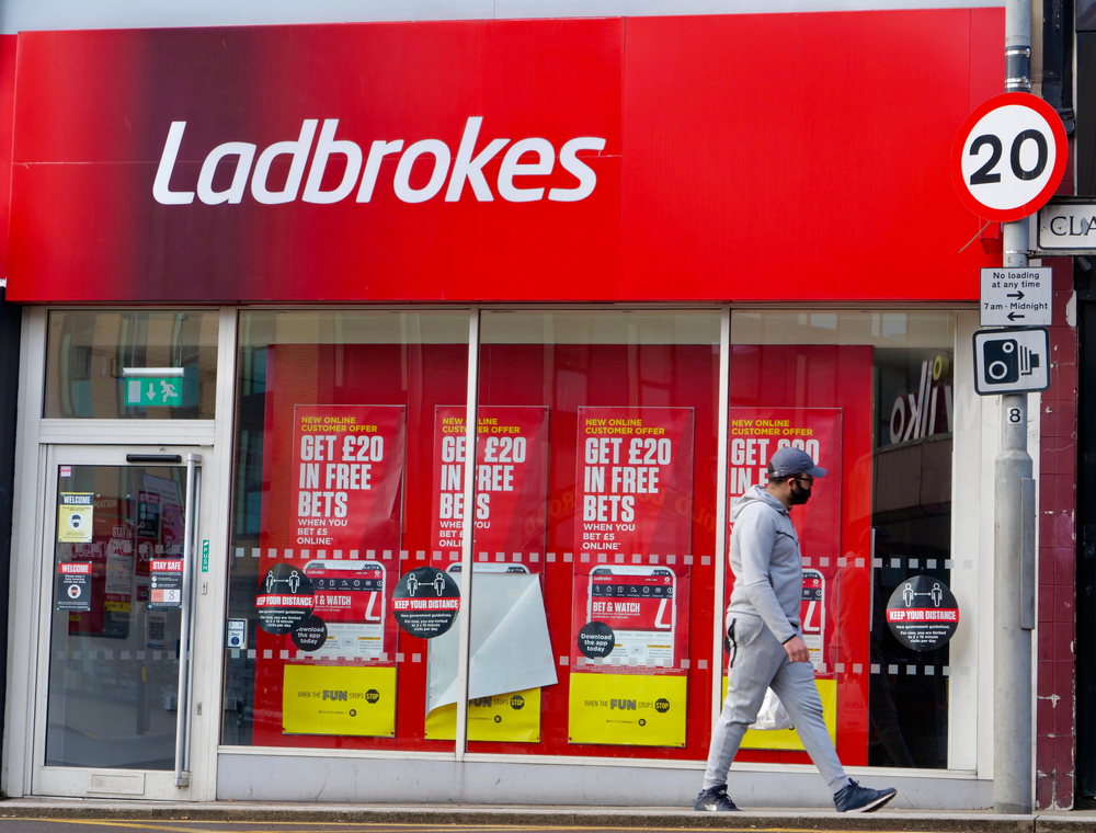 man in a face mask walks past a closed Ladbrokes betting shop in the UK