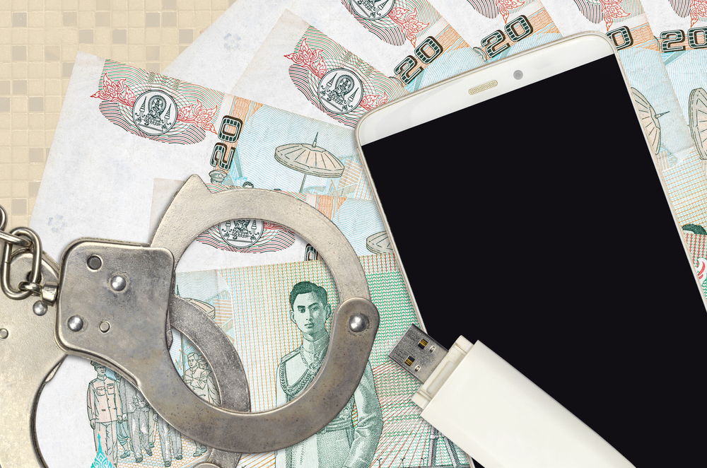 Thai baht notes, handcuffs, cellphone and pen drive