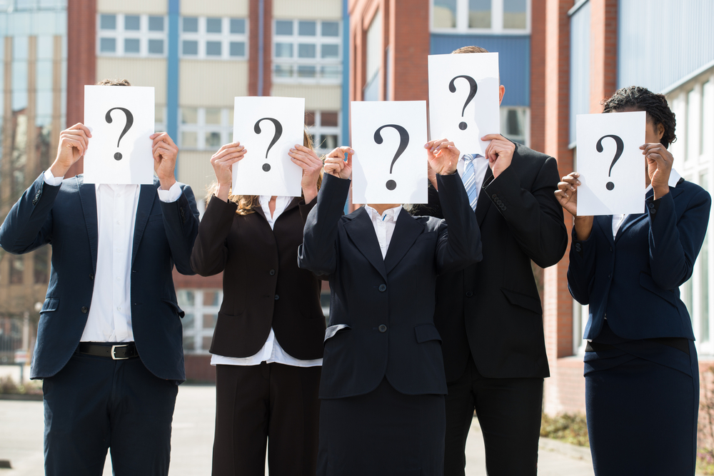 Five business people in formal office wear hold up sheet of paper with question mark in front of their faces