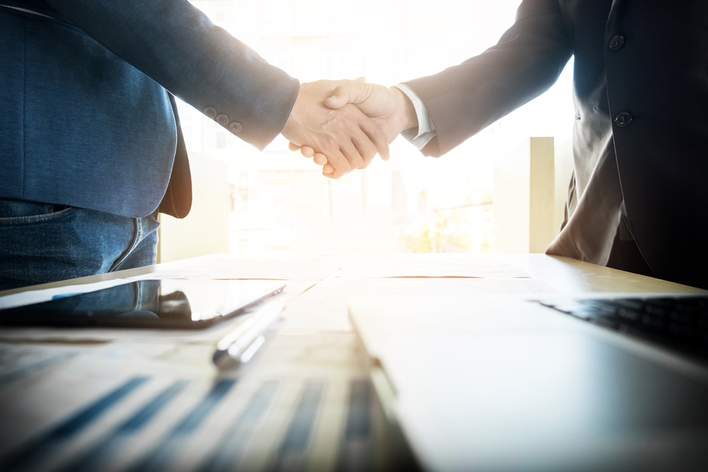 two businesspeople shaking hands as a gesture of agreement