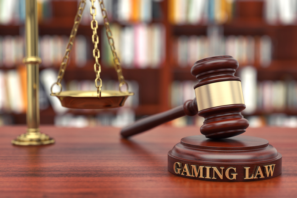 A judges gavel labeled with 'Gaming Law' next to scales