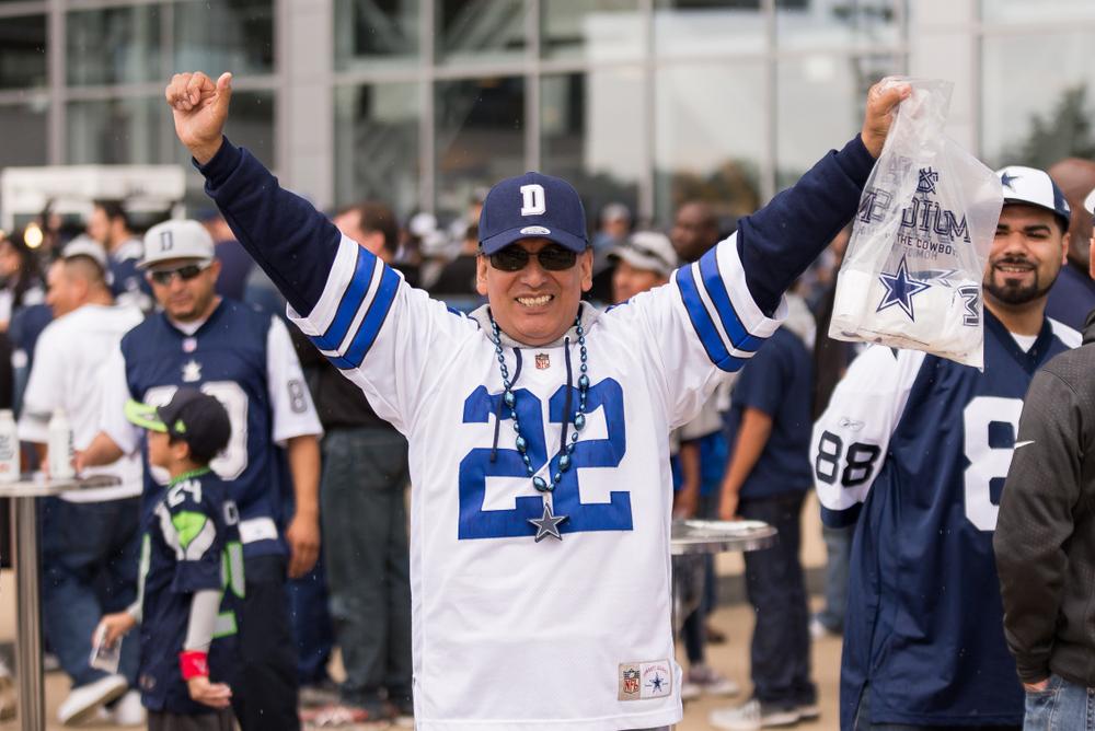 Dallas Cowboys fan in team gear with arms raised
