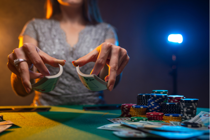 woman shuffling cards at a poker table