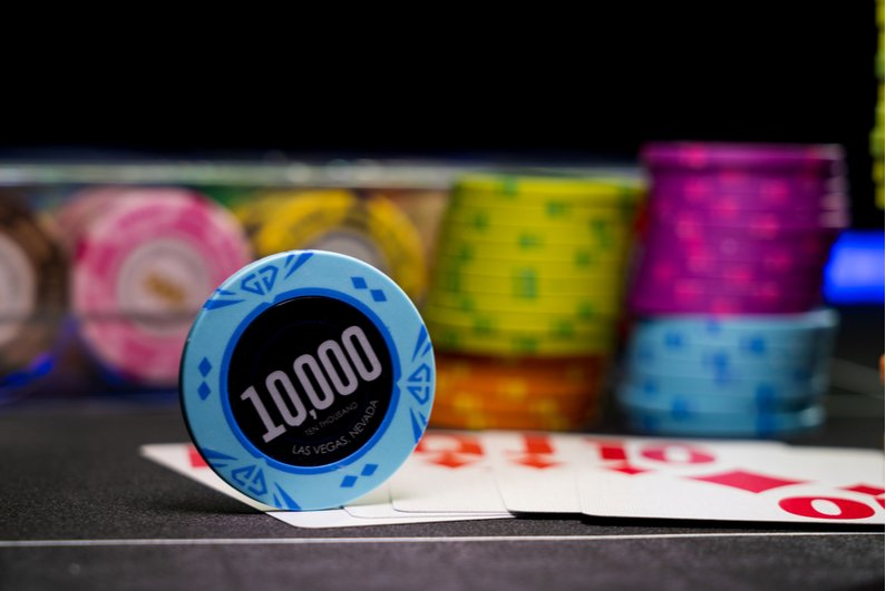 $10,000 chip on a poker table with stacks of chips in the background