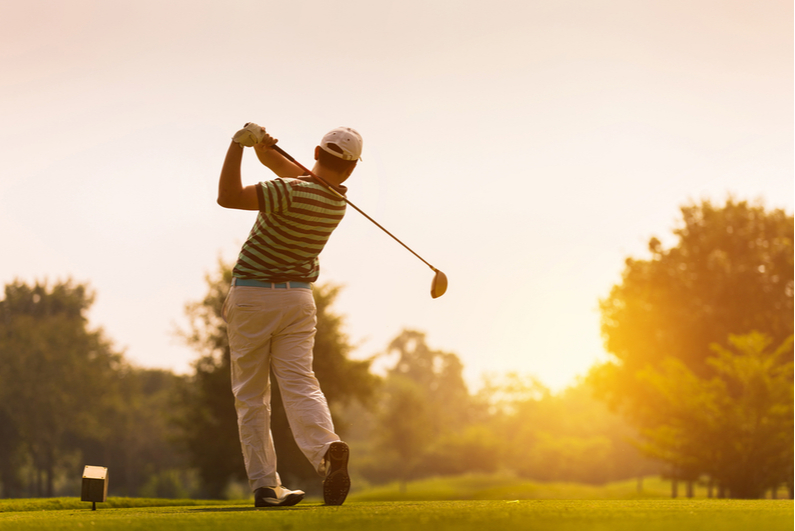 Golfer teeing off at sunset