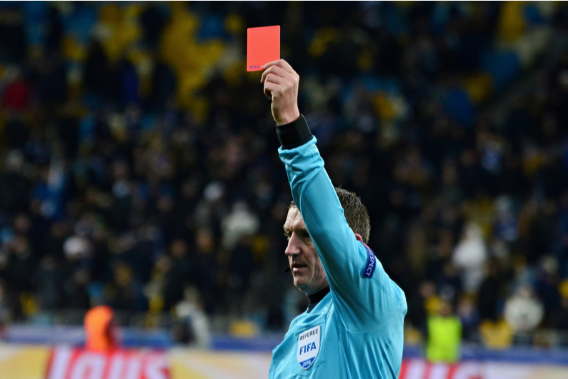 Soccer referee holding up a red card