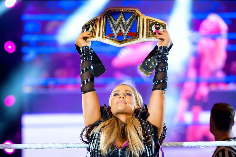 WWE wrestler Natalya holding up a title belt