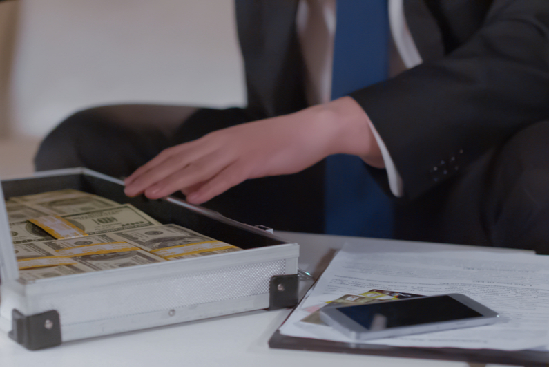 Businessman looking at cash in a briefcase