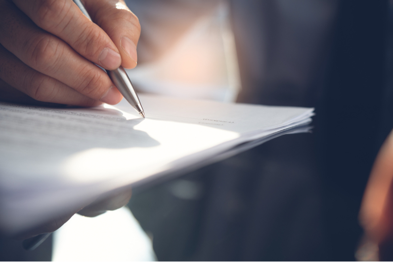 Closeup of person signing a contract