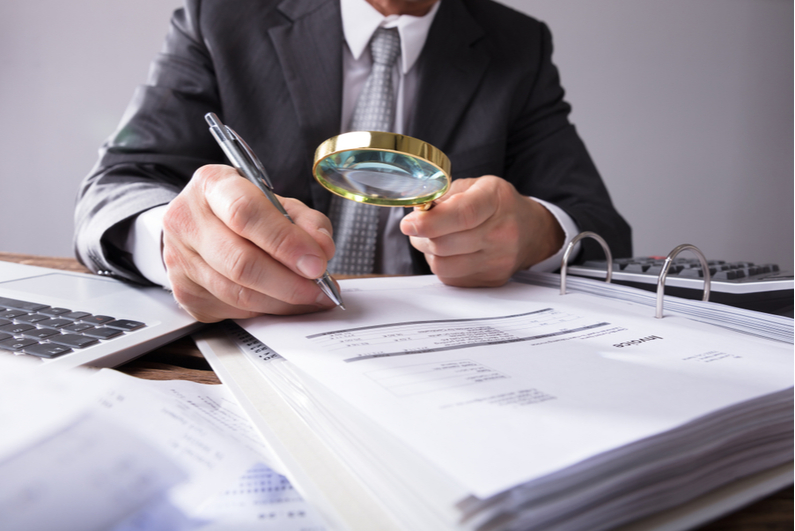 man examining documents with magnifying glass