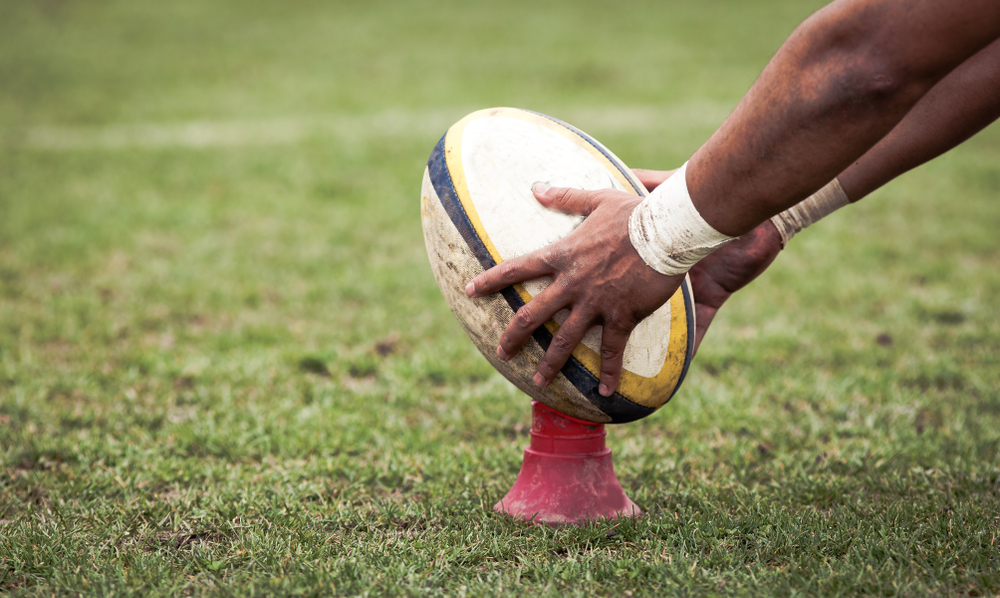 rugby player prepares to kick oval ball