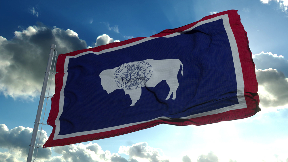 flag of Wyoming against blue sky backdrop