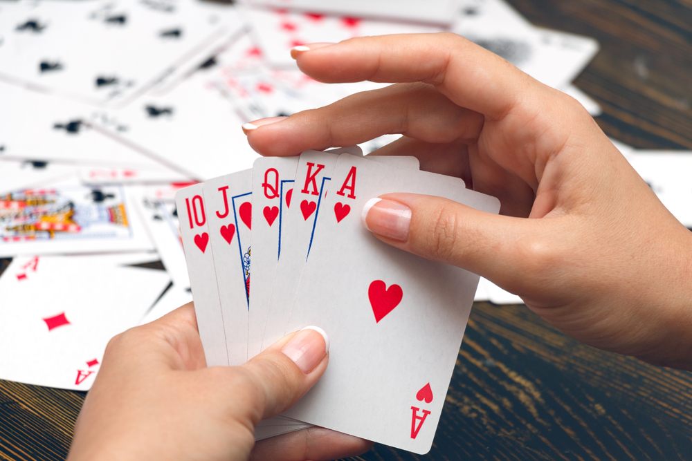female hands holding best poker hand
