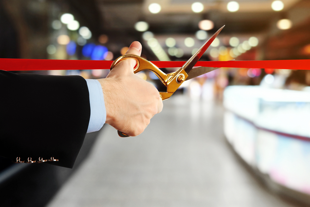 male's hand cuts ceremonial red ribbon at venue inauguration