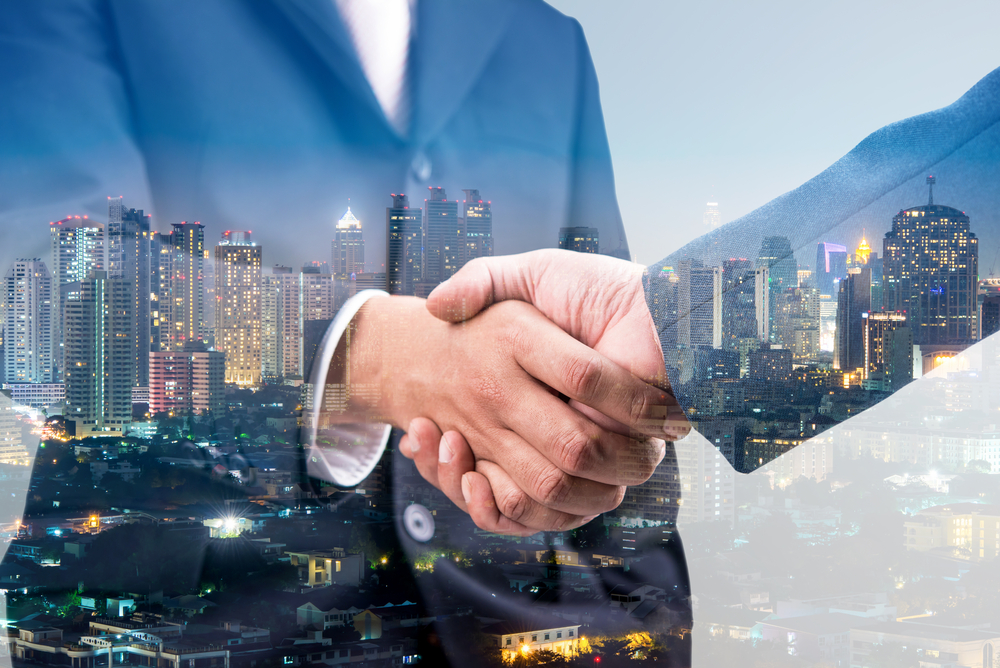 two businessmen shaking hands against a city nighttime backdrop