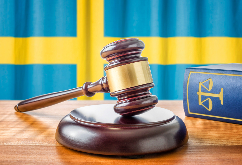 A judge's gavel in front of Swedish flag