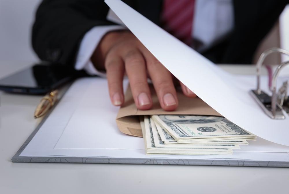 Businessman holds money in envelope between documents