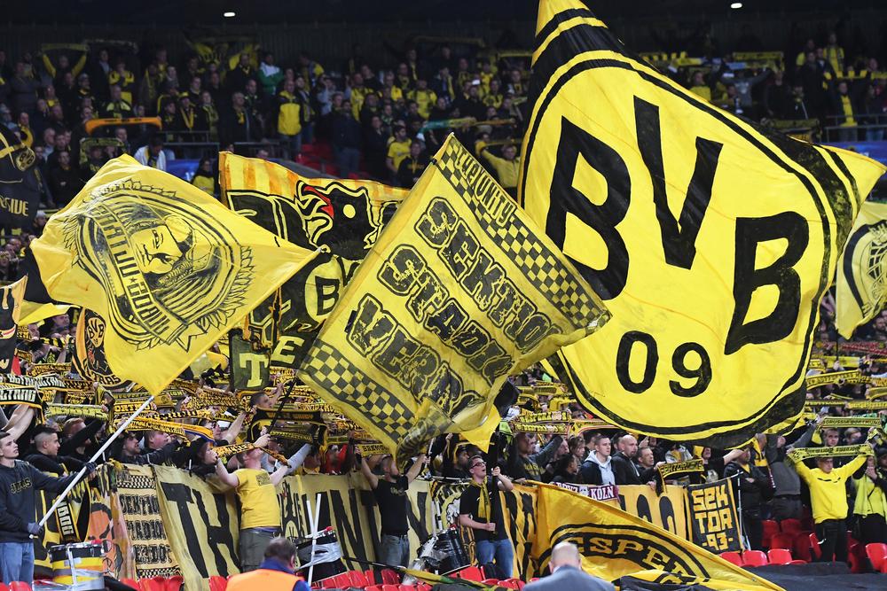 Borussia Dortmund fans waving club flags in soccer stadium