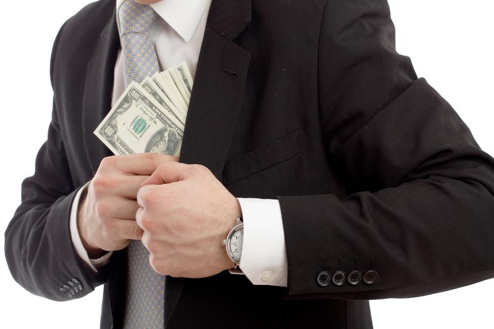 A businessman pocketing a wad of cash