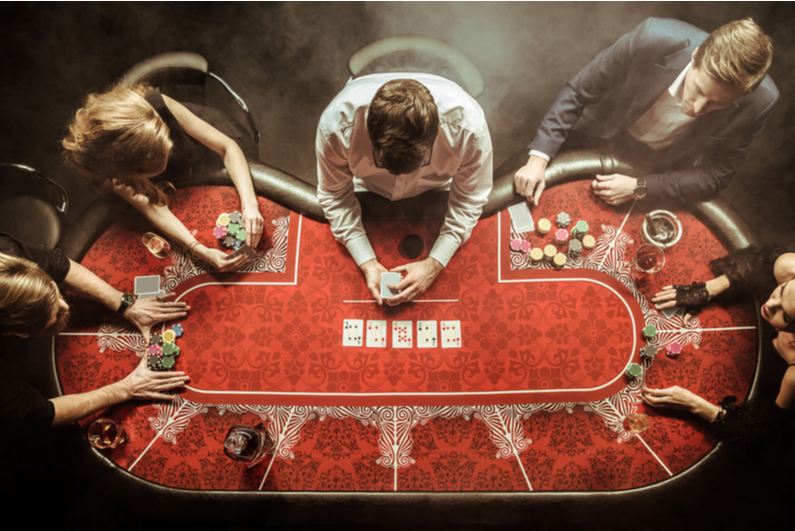 Top-down view of men and women playing poker