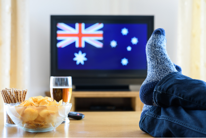 Person with feet propped up on a table with a TV in the background showing the Aussie flag