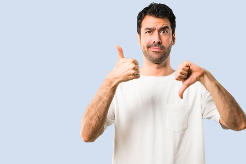 Man with a goofy, quizzical look on his face giving thumbs up and thumbs down