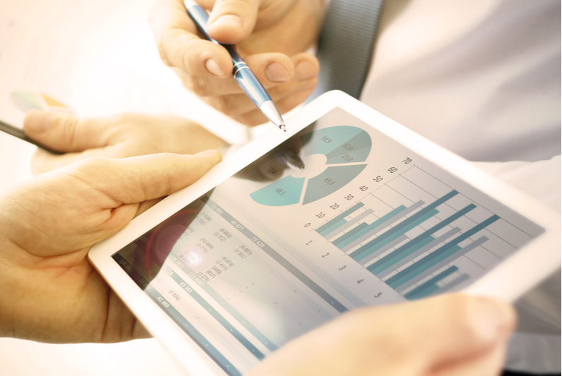 Closeup of two businesspeople looking at charts on a tablet