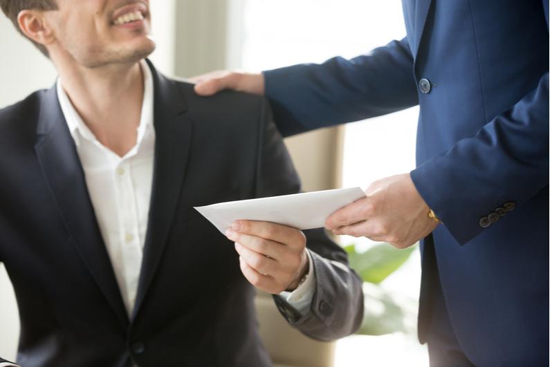 Boss handing employee a cash bonus in an envelope