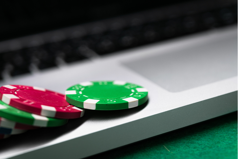 Closeup of laptop with poker chips