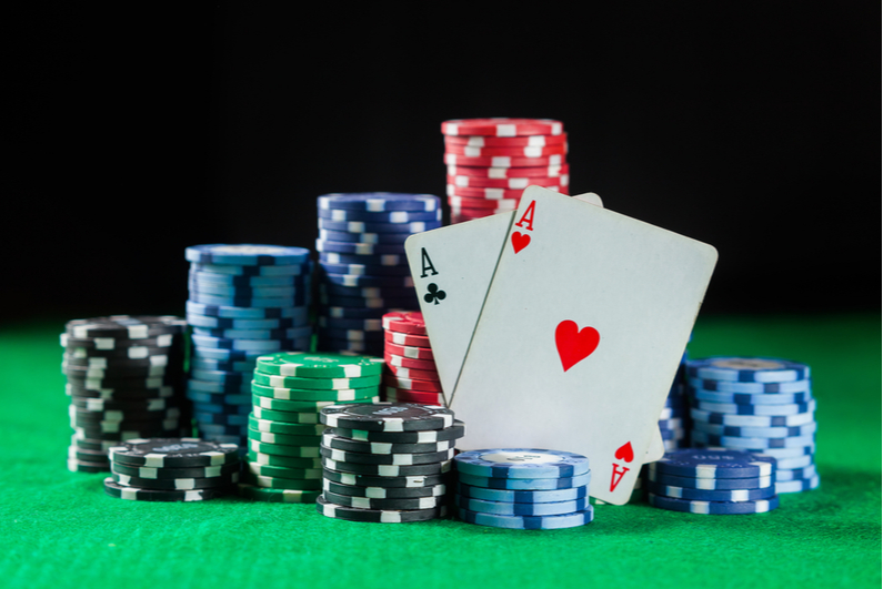 pair of Aces propped up against a stack of poker chips