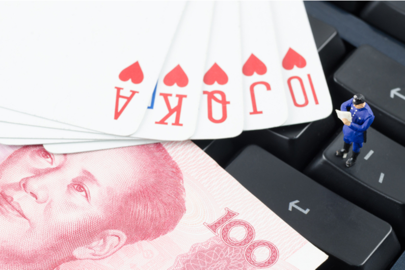 playing cards and Chines currency on a keyboard