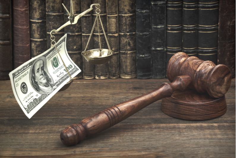 scales of justice with a $100 bill on one end