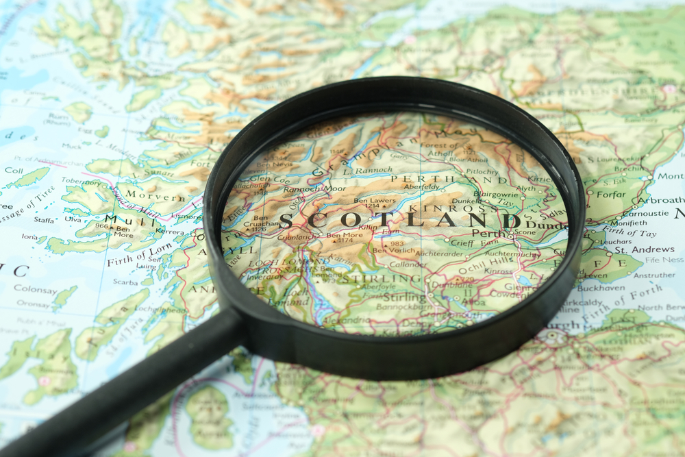 magnifying glass focuses on map of Scotland
